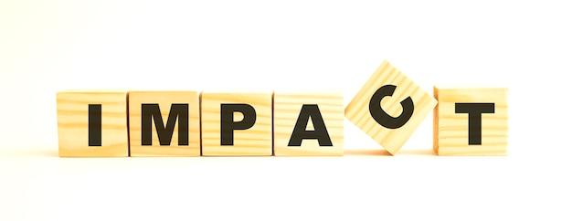 Het woord impact. houten kubussen met letters geïsoleerd op een wit oppervlak.