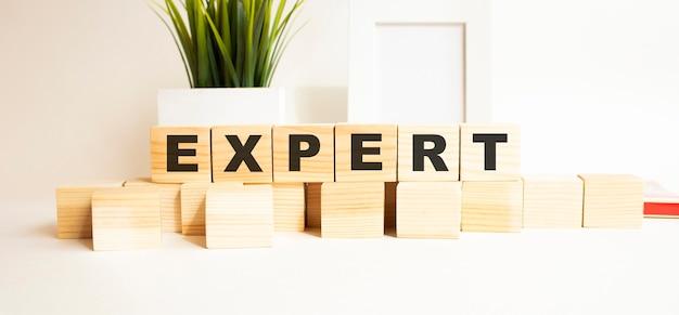 Het woord is expert. houten kubussen met letters op een witte tafel. wit oppervlak met fotolijst, kamerplant.