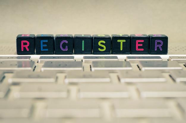 Het woord is register op de zwarte blokjes die op het grijze toetsenbord liggen. het concept van informatietechnologie en internet.