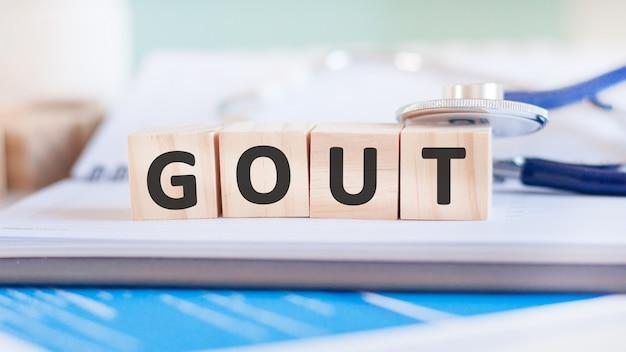 Het woord jicht is geschreven op houten kubussen in de buurt van een stethoscoop op een papieren oppervlak
