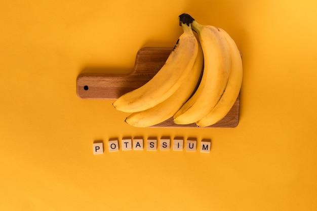Het woord kalium is opgebouwd uit houten blokken in het midden van bananen op een gele achtergrond