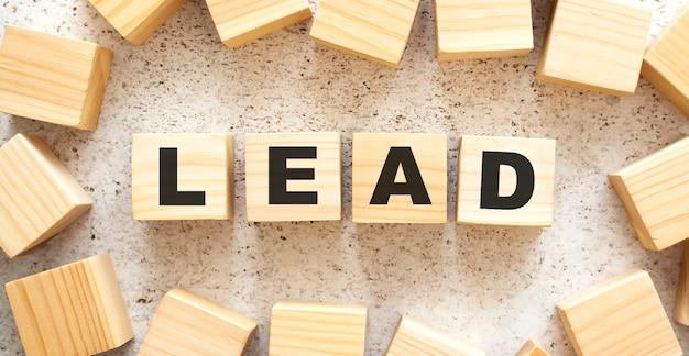 Het woord lead bestaat uit houten kubussen met letters, bovenaanzicht op een lichte achtergrond. werkruimte.