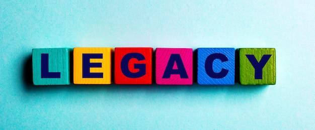 Het woord legacy is geschreven op veelkleurige heldere houten kubussen op een lichtblauwe achtergrond