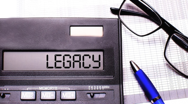 Het woord legacy staat in de rekenmachine naast een bril met een zwart montuur en een blauwe pen.