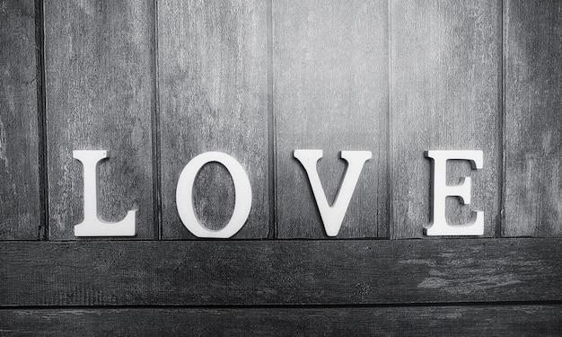 Het woord liefde bestaande uit witte houten letters op een houten achtergrond