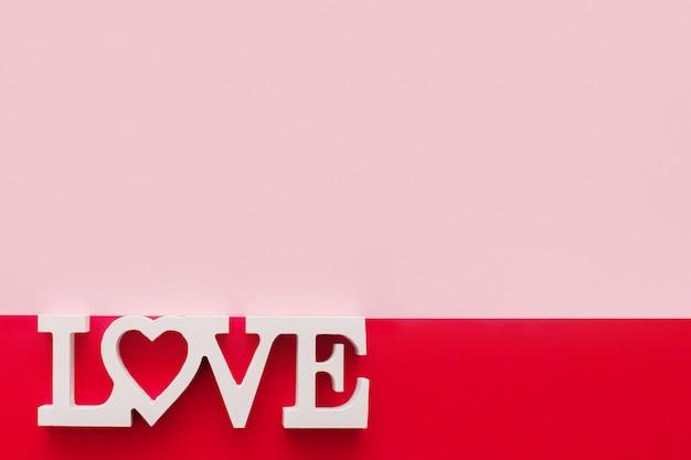 Het woord liefde bestaat uit houten letters op een roze en rode achtergrond, bovenaanzicht