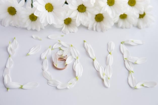 Het woord liefde gerangschikt door chrysanthemum bloemen. selectieve aandacht