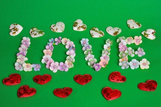 Het woord liefde is bekleed met letters op een schone groene achtergrond met kleurrijke bloemen aan de onderkant van het frame. bloemen van boven liggen in een lijn