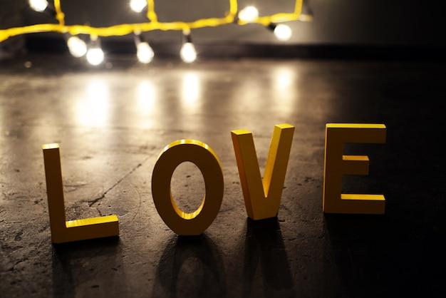 Het woord liefde met houten letters op de vloer met gloeilampen