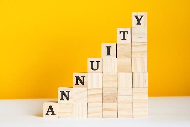 Het woord lijfrente is geschreven op een houten kubussen. blokken op een felgele achtergrond. corporate hiërarchie concept en multilevel marketing. selectieve aandacht.