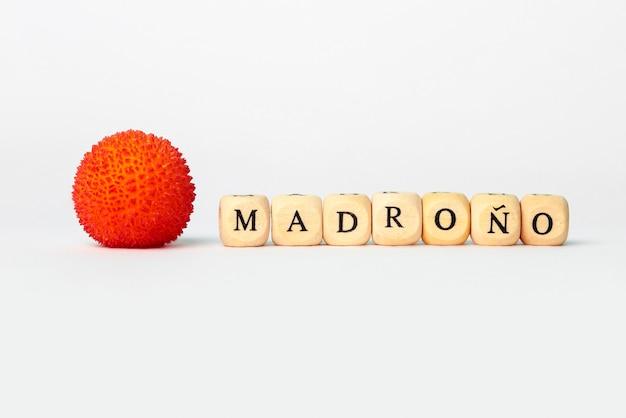 Het woord madronìo in houten kubussenbrieven naast aardbeiboomfruit op witte achtergrond isoleerde witte achtergrond