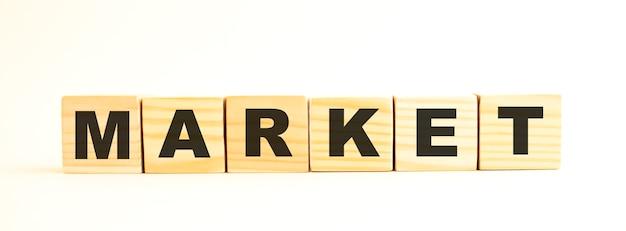 Het woord markt. houten kubussen met letters geïsoleerd op een wit oppervlak.
