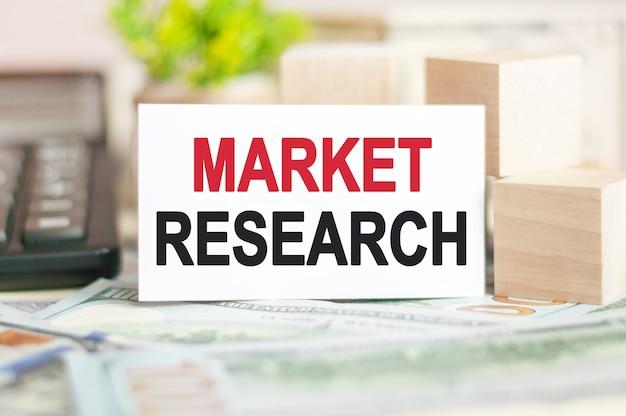 Het woord marktonderzoek is geschreven op een witte papieren kaart in de buurt van houten kubussen, rekenmachine op een bankbiljettenmuur. zakelijk en financieel concept