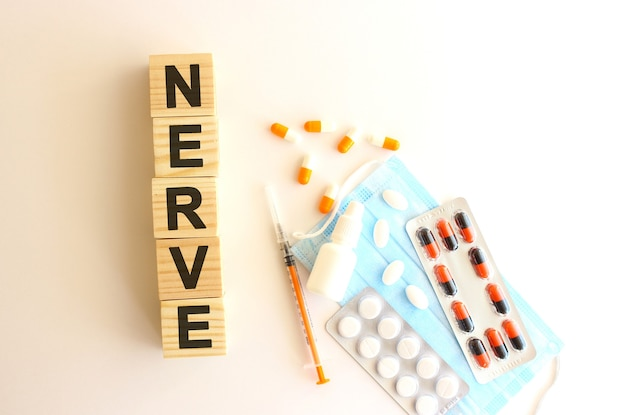 Het woord nerve is gemaakt van houten kubussen op een witte achtergrond met medicijnen en medisch masker.