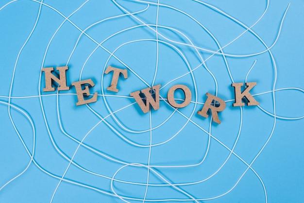 Het woord netwerk met houten letters in de vorm van een abstract spinnenweb, blauwe achtergrond