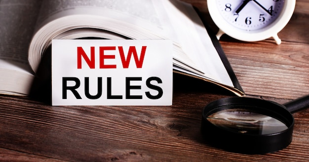 Het woord nieuwe regels geschreven op een witte kaart in de buurt van een open boek, een wekker en een vergrootglas