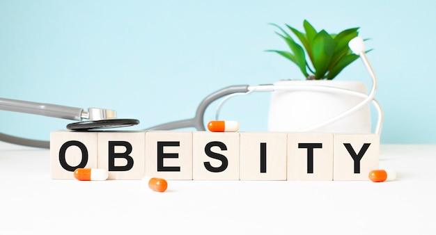 Het woord obesity is geschreven op houten kubussen in de buurt van een stethoscoop op een houten achtergrond. medisch concept