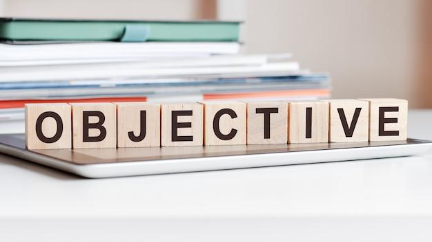 Het woord objectief is geschreven op houten kubussen die op een notitieblok staan, in het oppervlak een stapel documenten
