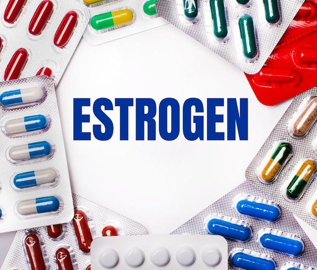 Het woord oestrogeen is geschreven op een lichte achtergrond omringd door veelkleurige pakketten met pillen. medisch concept