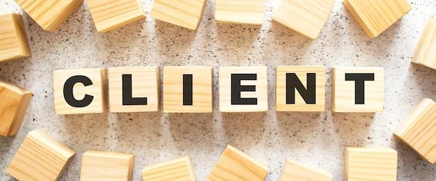Het woord opdrachtgever bestaat uit houten kubussen met letters, bovenaanzicht op een lichte achtergrond. werkruimte.