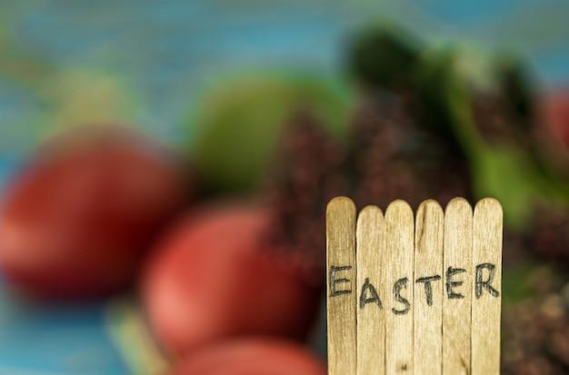 Het woord pasen in de conceptuele bloktekst op houten stokken, mooie feestelijke eieren met groenen