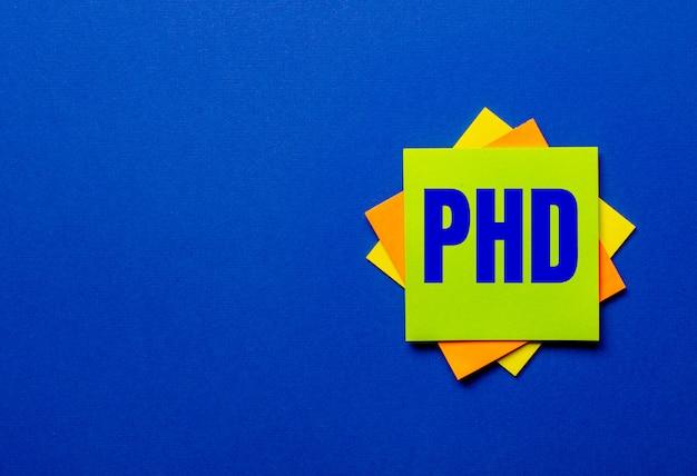 Het woord phd is geschreven op heldere stickers op een blauw oppervlak