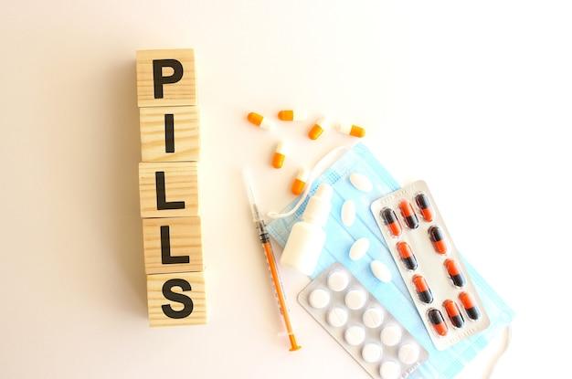 Het woord pills is gemaakt van houten kubussen op een witte achtergrond met medicijnen en medisch masker.