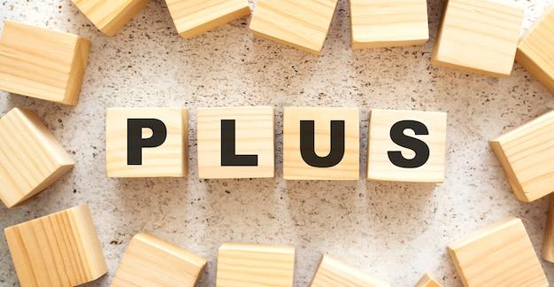 Het woord plus bestaat uit houten kubussen met letters, bovenaanzicht op een lichte achtergrond. werkruimte.