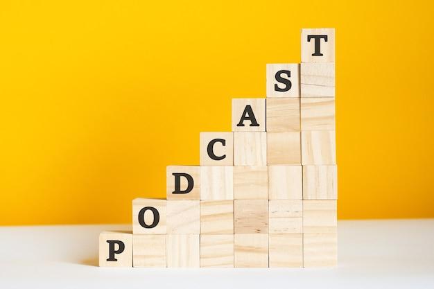 Het woord podcast is geschreven op een houten kubus. blokken op een felgele achtergrond. bedrijfshiërarchieconcept en marketing op meerdere niveaus. selectieve focus