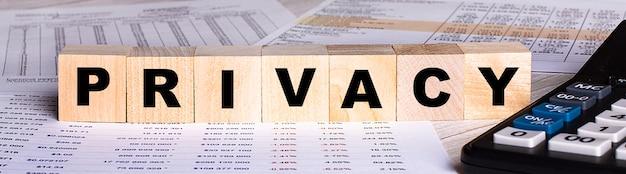 Het woord privacy is geschreven op houten kubussen in de buurt van de grafieken en rekenmachine.