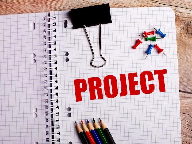 Het woord project is geschreven in een notitieboekje in de buurt van veelkleurige potloden en knoppen op een houten tafel.