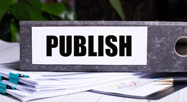 Het woord publiceren is geschreven in een grijze map naast documenten. bedrijfsconcept