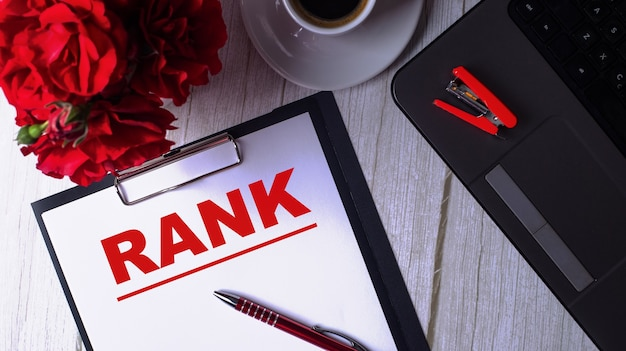 Het woord rank wordt in het rood geschreven op een wit blocnote dichtbij laptop, koffie, rode rozen en een pen.