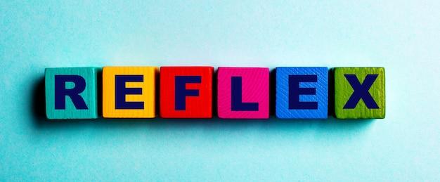 Het woord reflex is geschreven op veelkleurige heldere houten kubussen op een lichtblauwe achtergrond