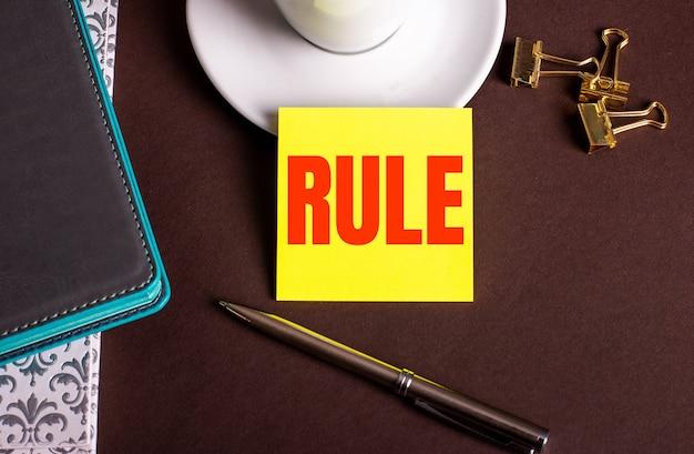Het woord regel geschreven op geel papier op een bruin oppervlak in de buurt van een koffiekopje en dagboeken