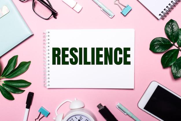 Het woord resilience is geschreven in een wit notitieboekje op een roze muur, omringd door zakelijke accessoires en groene bladeren.