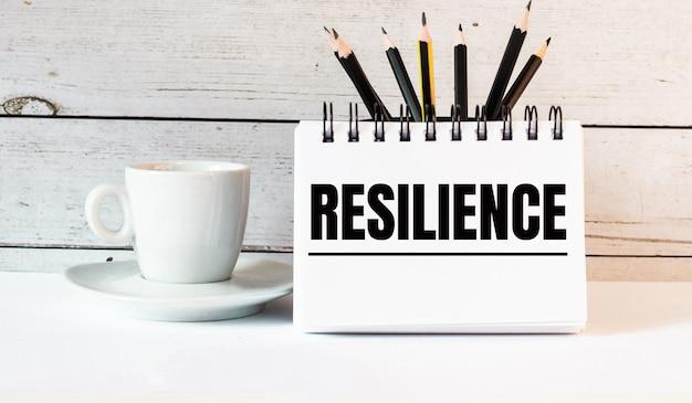 Het woord resilience staat in een wit kladblok naast een witte kop koffie op een lichte muur