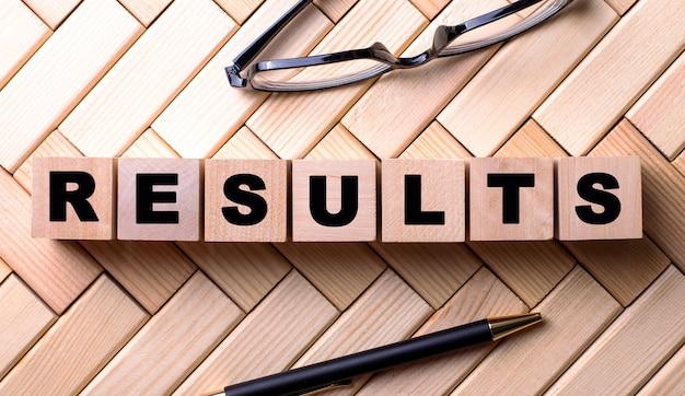 Het woord resultaten is geschreven op houten kubussen op een houten achtergrond naast een pen en een bril