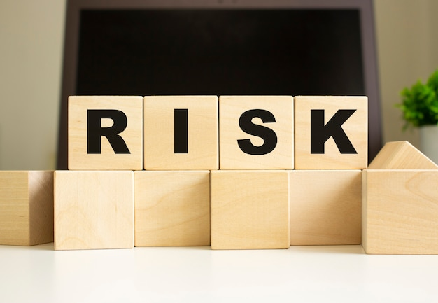 Het woord risico is geschreven op houten kubussen die op de kantoortafel voor een laptop liggen.