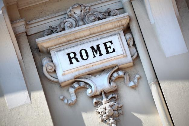 Het woord rome sneed in een oude gebeeldhouwde muur.
