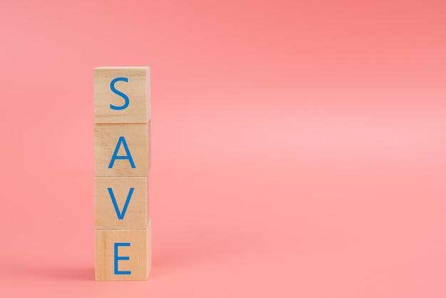 Het woord save op het houtblok op roze achtergrond