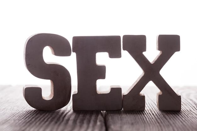 Het woord seks uit houten letters staat op tafel