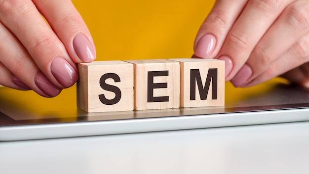 Het woord sem is geschreven op houten kubussen die op een notitieblok staan. zakelijk, onderwijs, financieel concept. sem - afkorting voor zoekmachine marketing