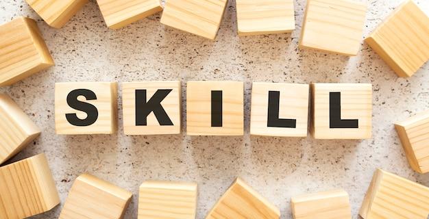 Het woord skill bestaat uit houten kubussen met letters, bovenaanzicht op een lichte ondergrond.