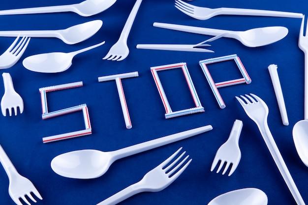 Het woord stop gemaakt van plastic buizen op blauw