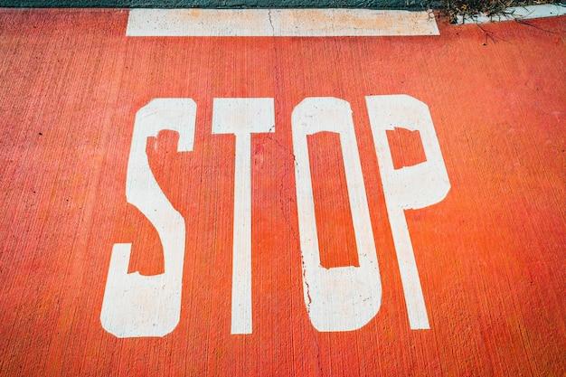 Het woord stop geschilderd in witte hoofdletters op een rode vloer.