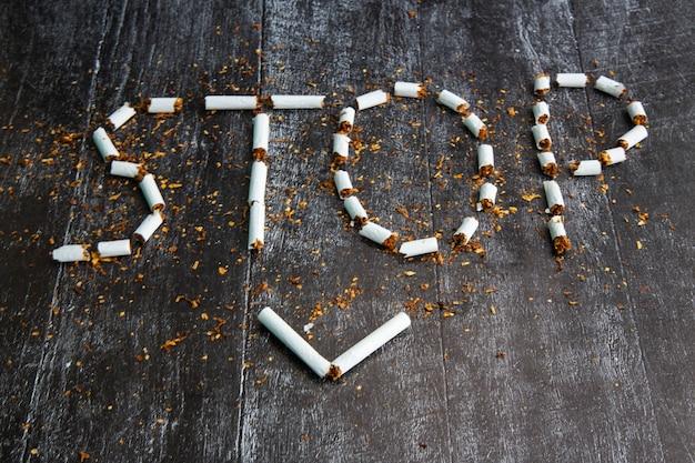 Het woord stop is geschreven met sigaretten op een donkere achtergrond. concept: schade van roken, stoppen met roken