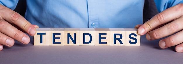 Het woord tenders bestaat uit houten kubussen door een man. bedrijfsconcept