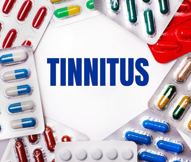 Het woord tinnitus is geschreven op een lichte achtergrond, omringd door veelkleurige pakketten met pillen
