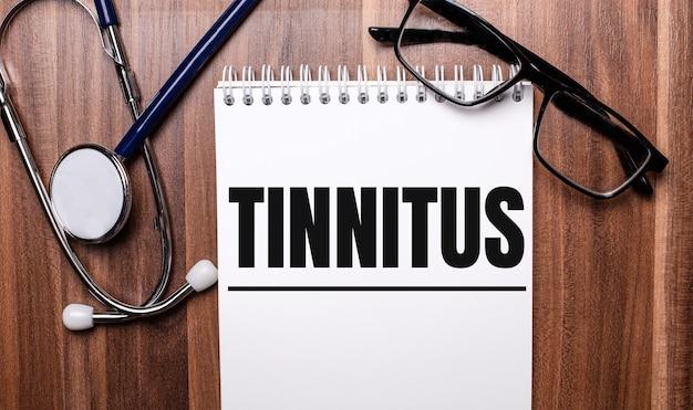 Het woord tinnitus is geschreven op wit papier op een houten oppervlak naast een stethoscoop en een bril met zwart montuur. medisch concept
